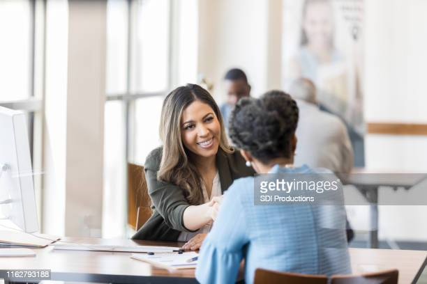 when the loan is processed, bank manager shakes customer's hand - bank manager stock pictures, royalty-free photos & images