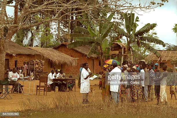 When the mobile team arrives in a village the villagers line up to have their necks examined for swollen glands
