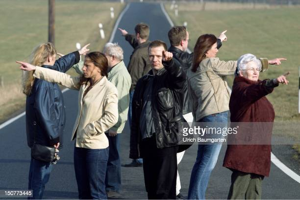 Which way Different aged people on a country road are pointing into different directions Symbol photo for 'future in Germany'