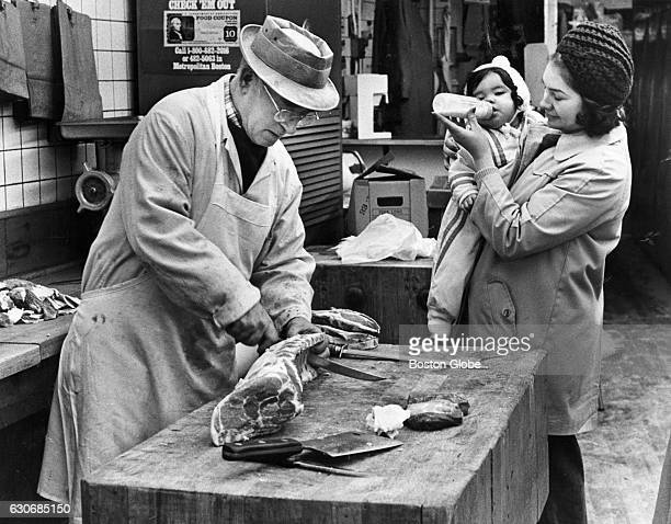 While 18monthold Norma Acebedo is kept otherwise occupied Clementine Acebedo of Jamaica Plain Mass watches butcher Harold Fishman cut her order of...