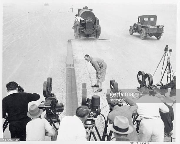 While a battery of cameras snap their shutters Sir Malcolm Campbell the well known English racing driver looks at the oil marker lining the one mile...