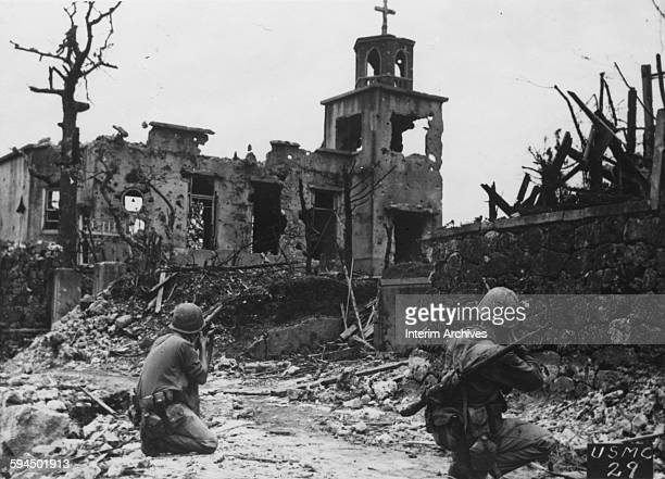 While a patrol moves in from the rear two United States Marines cover a Japanese sniper hiding in a church below Shuri Castle on Okinawa 1945 USMC...