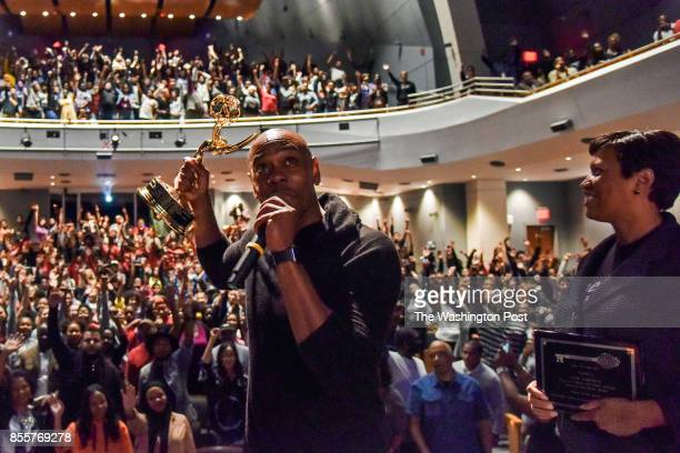 While addressing the students and faculty at the school he once attended comedian Dave Chappelle holds up his Emmy Award that he plans to donate to...