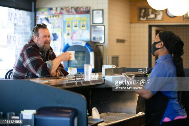 While an employee washes her hands, Ron Flexon sits at the counter for dine-in service at the Waffle House on April 27, 2020 in Brookhaven, Georgia....