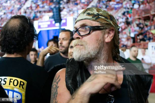 While attempting to remove Neil Makhija members of quotBikers for Trumpquot look in the direction US President Donald Trump on stage as they point...