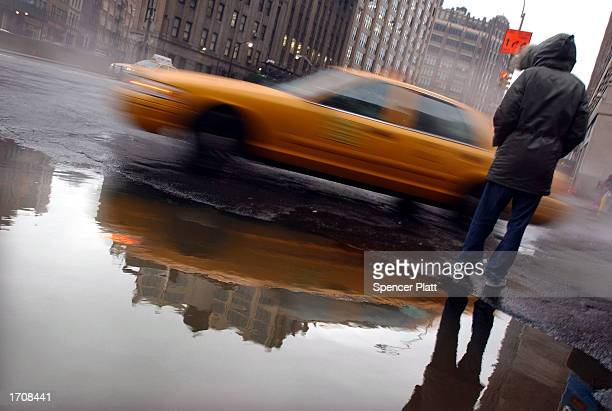 While avoiding a puddle a pedestrian attempts to cross the street during a rain and sleet storm January 3 2003 in New York City After a white...