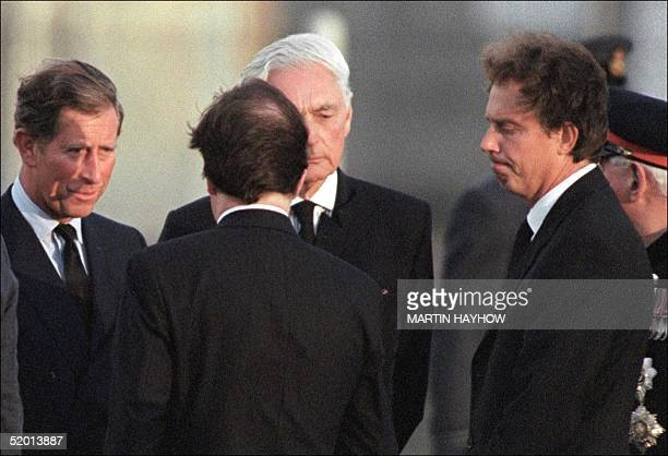 While Britain's Prince Charles receives condolences the British Prime Minister Tony Blair purses his lips at RAF Northolt near London 31 AUG...