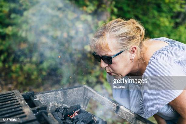 while camping in a canadian national park, a sixty year old woman is reviving a charcoal briquette fire blowing on charcoal briquettes to revive the fire needed to make dinner. - 63 year old female stock pictures, royalty-free photos & images