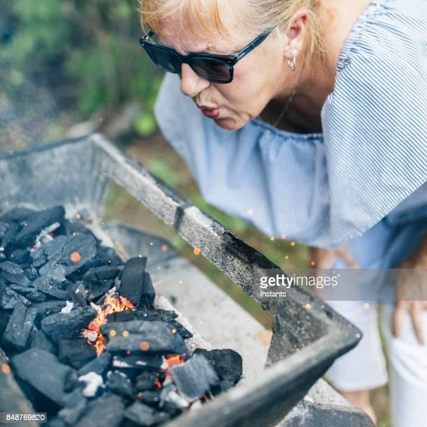 Beim camping in einem kanadischen Nationalpark, ist eine 60 jährige Frau Wiederbelebung Brandfall Holzkohle Brikett weht auf Holzkohlebriketts, das Feuer benötigt, um Essen zu machen wieder zu beleben.