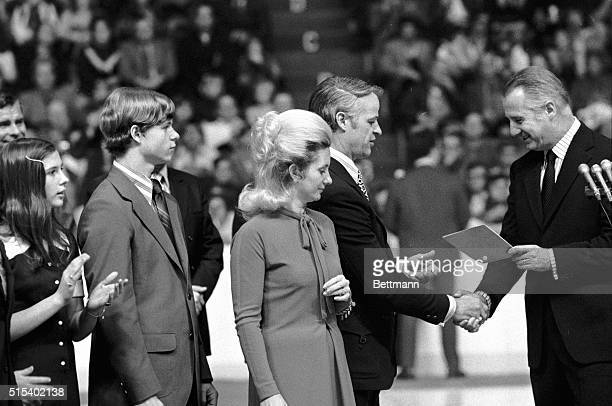 While Colleen Howe looks on, Vice President Spiro Agnew presents a letter of recognition from President Nixon to Gordon Howe during pre-game...