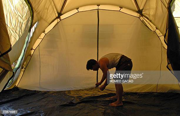 While Filipinos celebrate Christmas homeless Ariel Liaguno helps to set tup a tent at an evacuation center in a government school compound in Busay...
