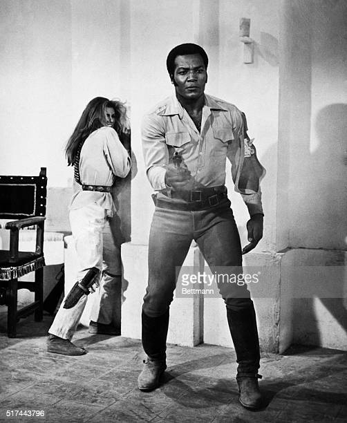 While football player turned actor Jim Brown fires his pistol at the camera actress Raquel Welch cowers against a wall in this movie still from '100...