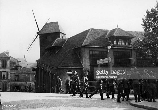 While German troops are occupying Paris after the French surrender these soldiers are visiting the Moulin de la Galette and its adjacent building a...