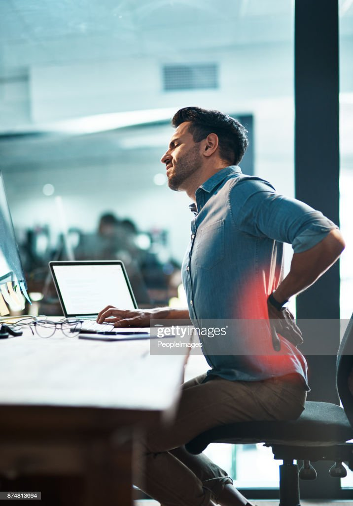 While he supports business, what's supporting his back? : Stock Photo