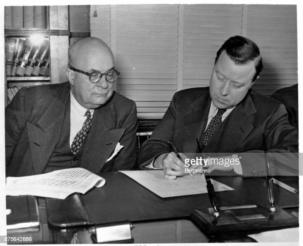 While Henry J Kaiser Chairman of the Board of KaiserFrazer Corporation looks on Walter P Reuther President of the UAW CIO signs an agreement covering...