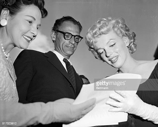 While her husband, playwright Arthur Miller looks on, actress Marilyn Monroe signs an autograph for a fan.