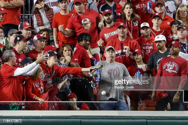 While holding two Bud Light beer cans, baseball fan, Jeff Adams, is hit in the chest with the home run ball hit by Yordan Alvarez of the Houston...
