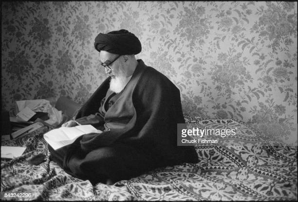 While living in exile, Iranian religious and political leader Ayatollah Ruhollah Khomeini sits cross-legged and reads a letter, Neuphe-le-Chateau,...