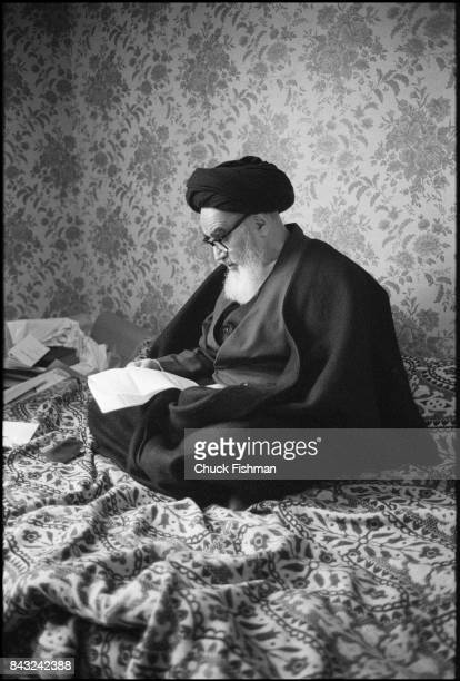 While living in exile Iranian religious and political leader Ayatollah Ruhollah Khomeini sits crosslegged and reads a letter NeupheleChateau France...
