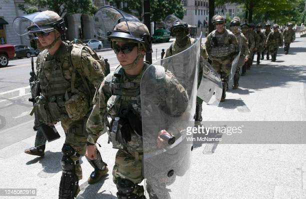While making their way to their posts for the day members of an airborne military unit tasked with crowd control move up 15th Street outside the US...