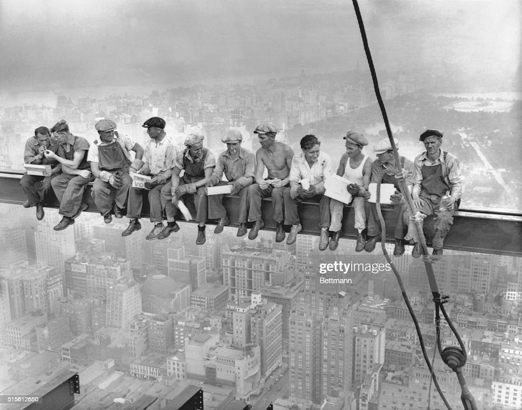 While New York's thousands rush to crowded restaurants and congested lunch counters for their noon day lunch, these intrepid steel workers atop the 70 story RCA building in Rockefeller Center get all the air and freedom they want by lunching on a steel beam with a sheer drop of over 800 feet to the street level. The RCA building is the largest office building in terms of office space in the world. (original caption). Image taken 9/20/32; filed 9/29/32.
