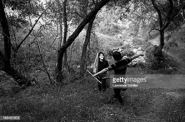 While on a daylong outdoor trip on LSD a young couple smile and carry musicial instruments Topanga Canyon California 1966