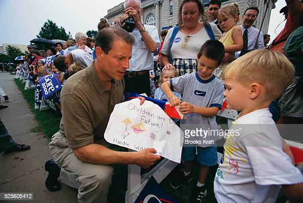"While on his presidential campaign, Vice President Al Gore talks with a child while holding a drawing that says, ""Children are the Future!"" Gore lost..."