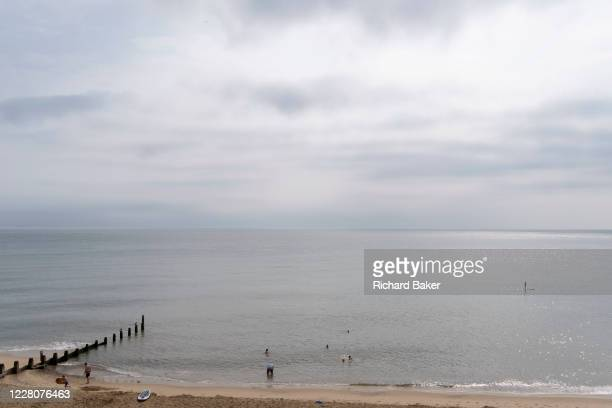 While other UK seaside resorts overcrowded during the Coronavirus pandemic, staycationers enjoy calm seas on the Norfolk coast, on 14th August 2020,...