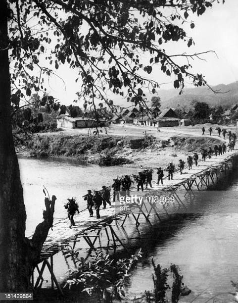 While Paris' peace talks are marked time members of FNL resistance crosse a bridge 17 November1968 in Laos during the Vietnam war which was extended...