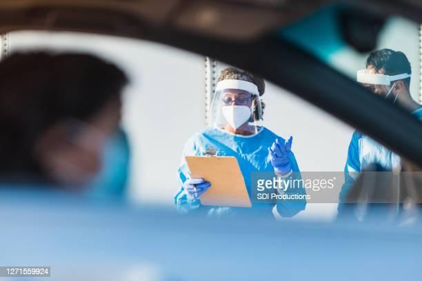 患者が車の中で待っている間、医療従事者は主張する - ドライブスルー検査 ストックフォトと画像