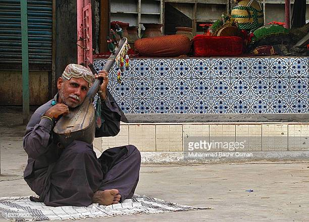 CONTENT] While playing with his musical instrument one of the folk singer singing the religious poetry outside there the shrine of Shah Noorani...
