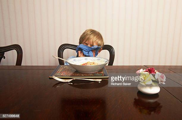 While seated to have dinner at home a young boy of about 10 years of age hides his face and wipes his lips with a serviette Demonstrating perfect...