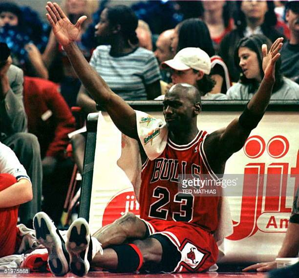 While sitting by the scorers table before returning to play, Michael Jordan of the Chicago Bulls celebrates after a teammate scored a three point...