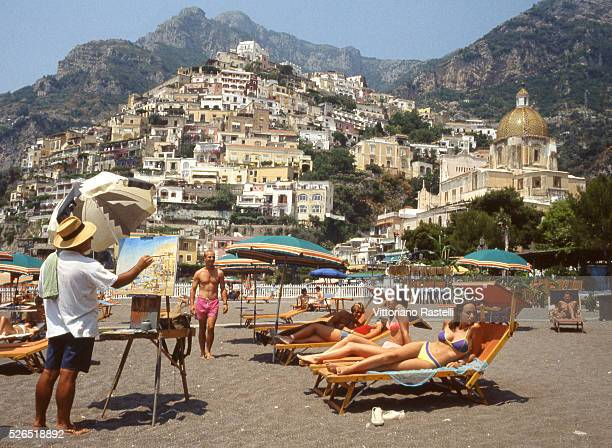 While sunbathers enjoy beach life a painter portrays the landscape of Positano one of the prettiest villages on the Amalfi coast near Naples