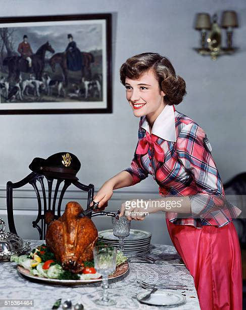 While the men are fighting in World War II actress Phyllis Thaxter cuts the holiday turkey A military hat sits on an empty chair perhaps waiting to...