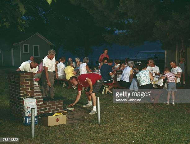 While three men struggle with an outdoor brick cooker a large group of people sit at picnic tables near the waterfront at the Perkins Cabins motel...
