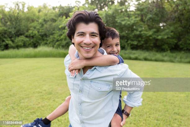 while uncle carries nephew, both smile for camera - nephew stock pictures, royalty-free photos & images