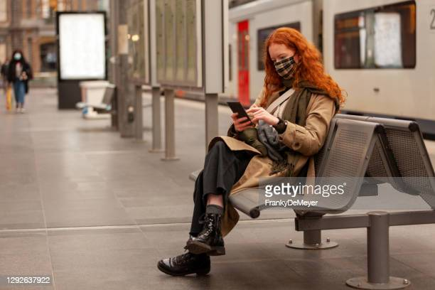 while waiting for her commuter train to arrive a young curly red haired student swipes on het mobile phone - belgium stock pictures, royalty-free photos & images