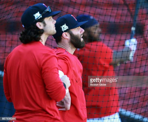 While waiting for their turn in the cage Boston Red Sox players Andrew Benintendi left and Dustin Pedroia center watch the flight of a ball hit by...