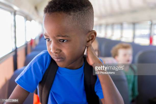 while waiting to get off bus, boy worries about school - only boys stock pictures, royalty-free photos & images