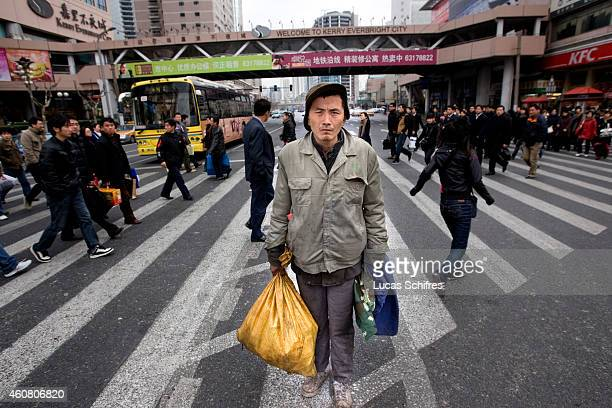 While wealthier Shanghai inhabitants cross the street Wu Wenyi poses for a photograph on February 17 2009 in Shanghai China Wu Wenyi came to Shanghai...