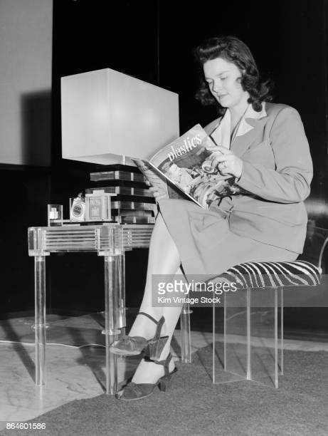 Whilst reading a magazine about plastics a model sits on a plastic chair next to a plastic table on which can be seen a plastic lamp during a...