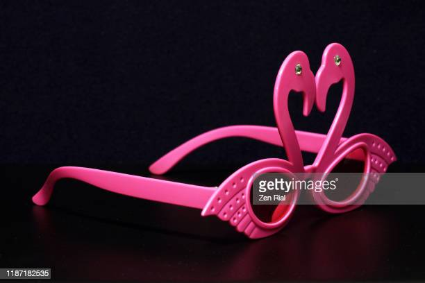 whimsical pair of pink plastic flamingo-shaped party eyeglasses isolated on black background - flamingo heart stock pictures, royalty-free photos & images