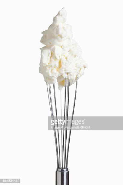 Whipped cream on whisk against white background