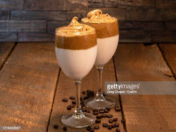 whipped dalgona coffee latte in a stem glass on a wooden background and coffee beans spread around. - dalgona stock pictures, royalty-free photos & images