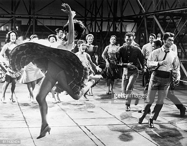 Whirling wildly and kicking up her heels, Rita Moreno, as Anita, dances with members of a Puerto Rican gang and their girlfriends support in a scene...