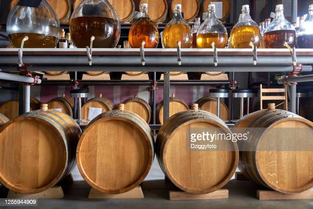 whiskey barrels in cellar - bourbon whiskey stock pictures, royalty-free photos & images