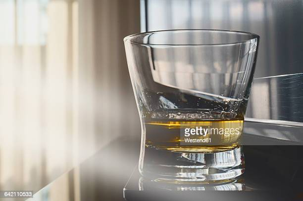 Whiskey glass in front of window, morning light and TV