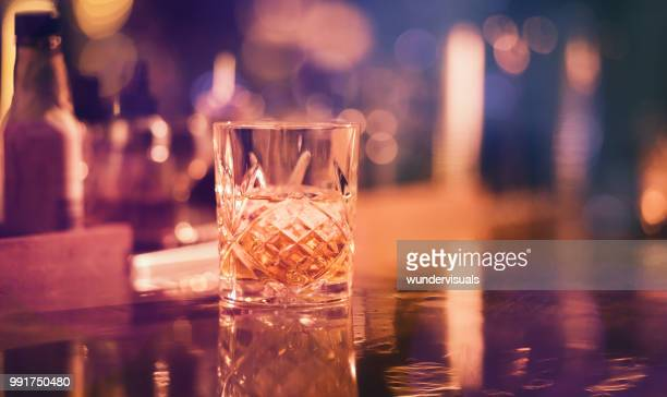 whiskey on the rocks served in vintage glass at bar - scotch whiskey stock pictures, royalty-free photos & images
