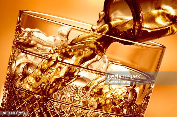 whiskey pouring into glass, close-up - alcohol stock pictures, royalty-free photos & images